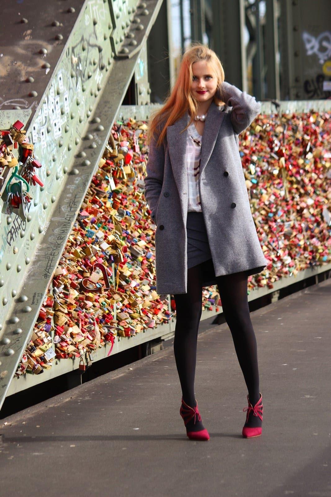 Day to Night Look mit grauem Mantel auf der Hohenzollernbrücke