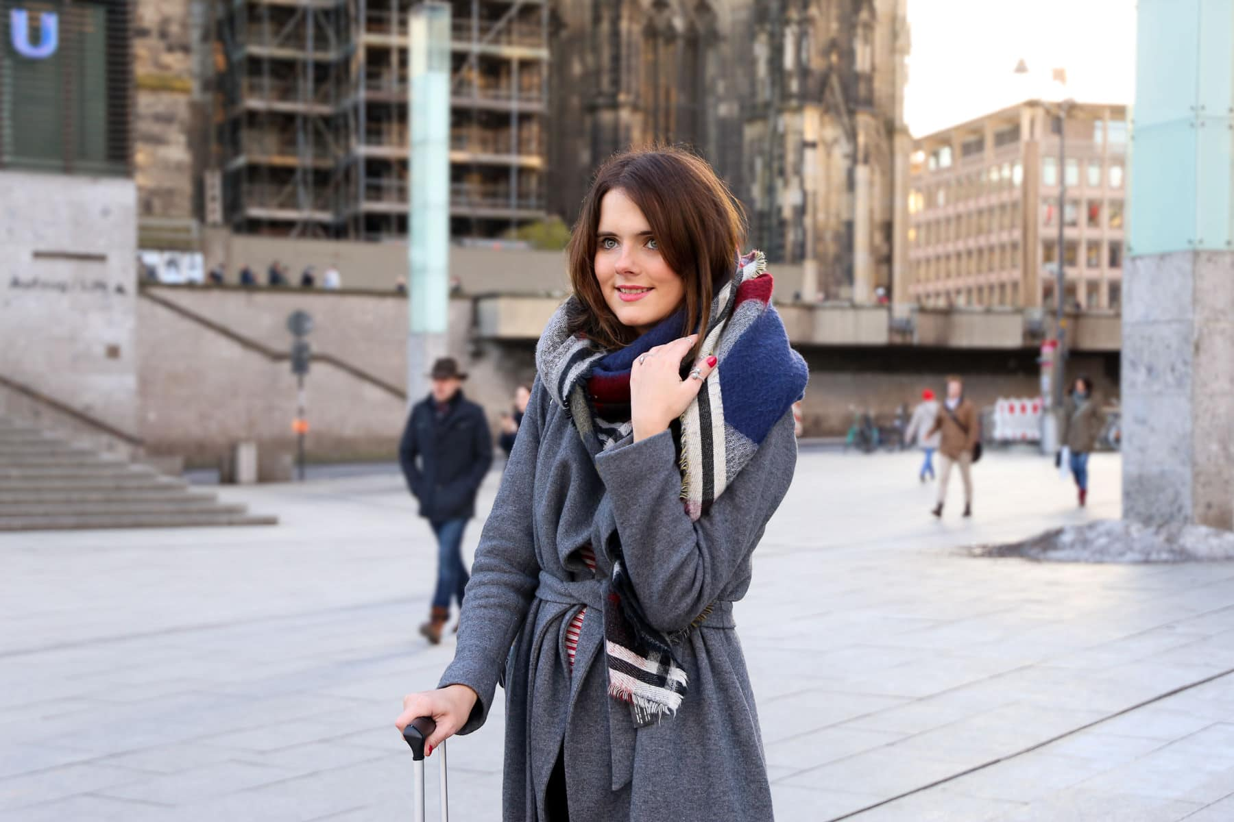 Travel Fashion Look am Kölner Dom: Grauer Mantel & roter Koffer